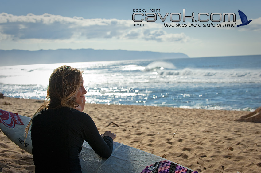 A girl studies the waves with surf board in hand